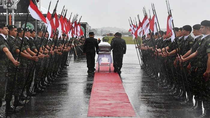 A military guard of honor receives the coffins of the members of the Chapecoense Real football club team killed in a plane crash in Colombia, upon their arrival at the airport of Chapeco, in Santa Catarina, southern Brazil, on December 3, 2016.  The first of two Brazilian air force planes carrying the remains of a football team killed in a plane crash arrived Saturday in the city of Chapeco in southern Brazil. / AFP PHOTO / Nelson Almeida