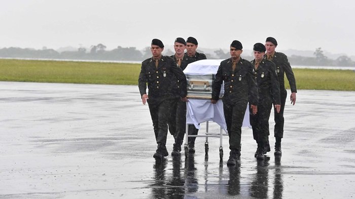 The coffin of one of the 50 members of the Chapecoense Real football club team killed in a plane crash in Colombia, is downloaded upon their arrival at the airport of Chapeco, in Santa Catarina, southern Brazil, on December 3, 2016.  The first of two Brazilian air force airplanes carrying the remains of a football team killed in a plane crash arrived Saturday in the city of Chapeco in southern Brazil. / AFP PHOTO / Nelson Almeida